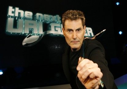 Israeli psychic Uri Geller poses with a spoon which he bent for photographers in Cologne January 6, 2008. The famed 'spoon-bender' Geller, who burst on the world scene in the 1970s with telekinetic performances starts a new television show 'The next Uri Geller' in Germany on January 8, 2008.  REUTERS/Ina Fassbender  (GERMANY) - RTX59UF