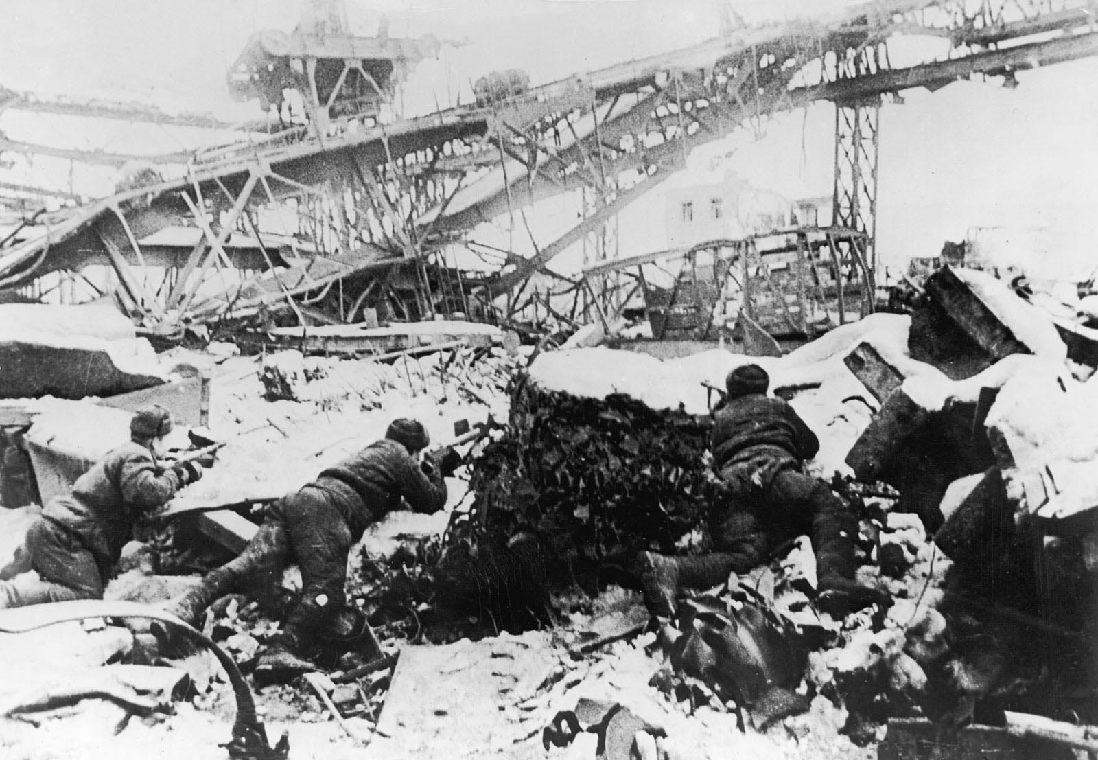 circa 1942:  Russian soldiers aim their rifles from behind snow-covered rubble as they defend the 'Krasnye Oktyabr' (Red October) factory from German troops during the Battle of Stalingrad in World War II, Stalingrad (now Volgograd), USSR (now Russia. The German troops intended to win the factory as a Christmas present for Hitler, but the Russian troops held it for the duration of the conflict.  (Photo by Hulton Archive/Getty Images)